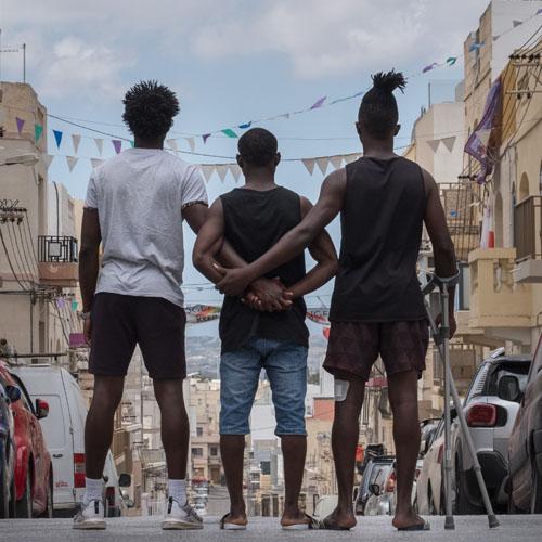 Drei Männer stehen nebeneinander mit dem Rücken zu dem*der Fotograf*in auf einer Straße und schauen auf eine Stadt. Sie haben die Arme umeinander gelegt.
