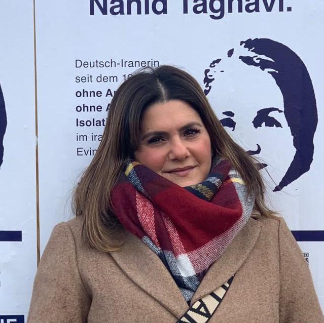 Porträtbild von Mariam Claren, mit Schal, vor einer Wand mit Plakaten, die die Freilassung ihrer Mutter fordern