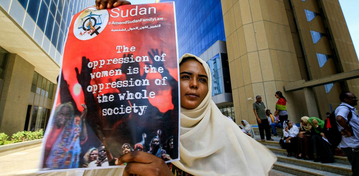 "Das Bild zeigt eine Frau mit Kopftuch, die ein Plakat in der Hand hält mit der Aufschrift ""The oppression of women is the oppression of the whole society"""