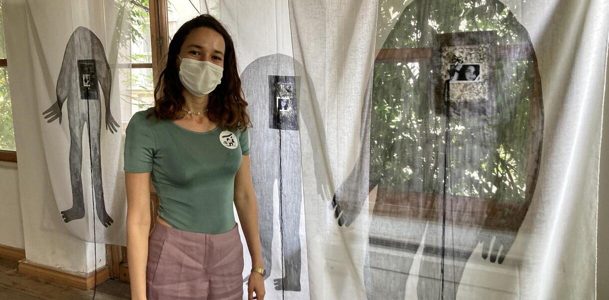 Eine Frau mit Mundnasenschutz steht in einem AUsstellungsraum vor aufgehängten Stofftüchern, die bemalt sind.