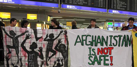 """Mehrere junge Männer halten Transparente hoch mit Zeichnungen und dem Slogan """"Afghanistan is not safe!"""", im Hintergrund ist eine Anzeigetafel zu sehen mit den Zeiten der Abflüge vom Flughafen"""