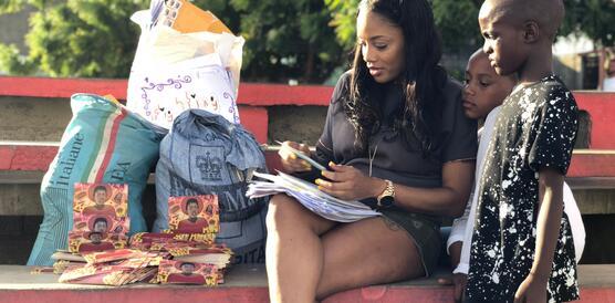 Eine Frau sitzt auf einer roten Bank und liest Briefe, neben ihr stehen große Taschen mit weiteren Briefen und zwei Kinder