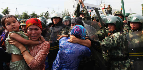 Eine verzweifelte Frau mit Kind auf dem Arm, zwei weitere Frauen, umringt von Polizisten in Tarnkleidung und mit erhobenen Schlagstöcken