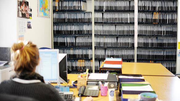 Schreibtisch voller akten  Menschen im Minutentakt | Amnesty International
