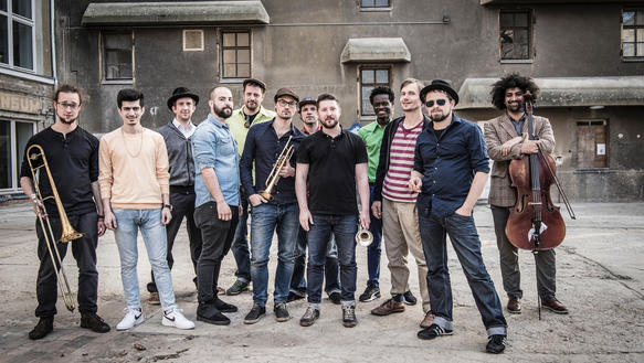 "Gruppenfoto der Band ""Banda Internationale"" in einem Innenhof"