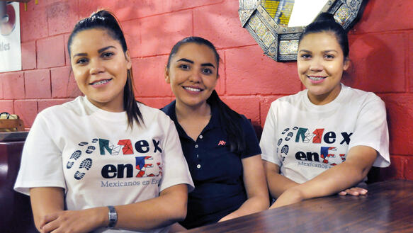 Die drei Schwestern Citlali, Deisy und Paola Alvarado sitzen lächelnd  nebeneinander an einem Tisch, zwei von ihnen sind eineiige Zwillinge
