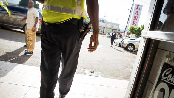 Unterkörper eines Mannes in grauer Hose und gelber Warnweste, an seinem Gürtel befindet sich eine Pistole