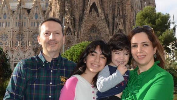 Ein Mann in einem kariertem Hemd posiert mit seinen zwei Kindern und Frau vor einer Kathedrale