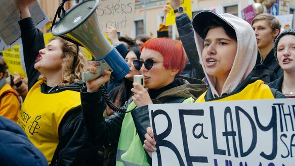 Verschiedene Menschen, darunter Amnesty-Unterstützende mit gelben Westen und dem Amnesty-Logo demonstrieren, eine Frau trägt ein Megaphon.