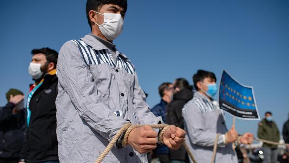 Das Bild zeigt eine Protestaktion: Ein Mann mit gefesselten Händen und grauer Gefängniskleidung steht auf einem öffentlichen Platz.