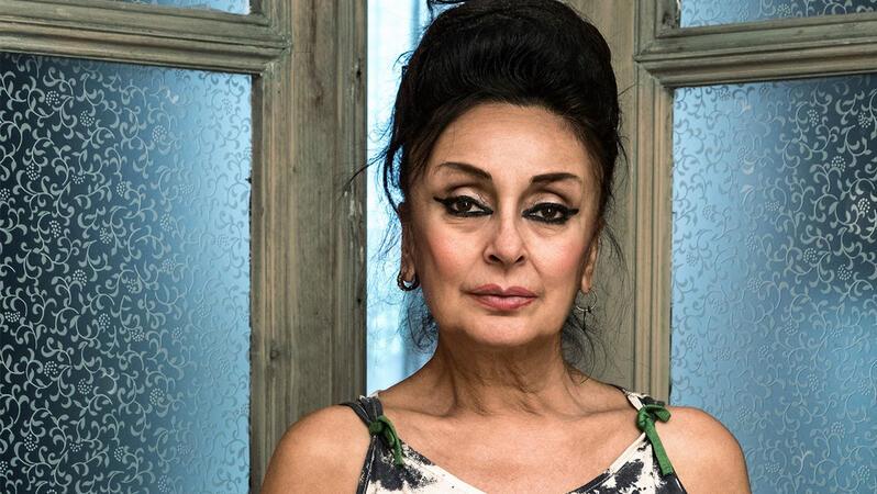 Eine Frau mittleren Alters schaut in die Kamera. Ihre Augen sind stark schwarz geschminkt. Im Hintergrund sieht man eine Holzglastür.