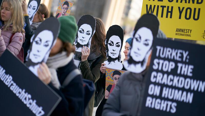 Eine Gruppe von Personen steht vor dem Brandenburger Tor und trägt Pappmasken mit dem Gesicht von Eren Keskin und hält Schilderin den Händen.