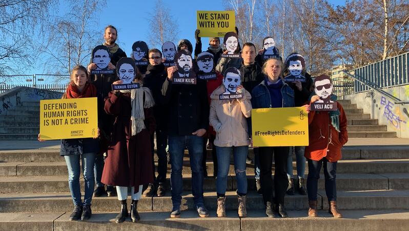 Eine Gruppe Menschen steht auf einer breiten Treppe. Einige tragen Schilder mit Texten, andere halten sich Schwarz-Weiß-Fotos von Gesichtern vor das Gesicht.