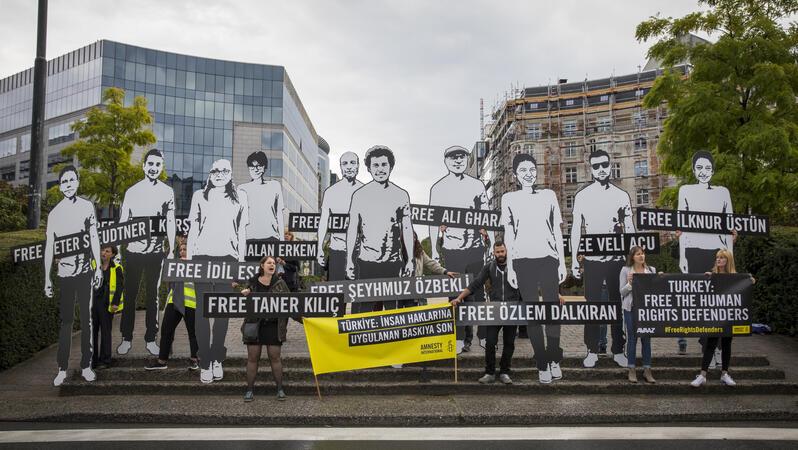 Mehrere Personen demonstrieren, stehen auf einer Treppe mit mehreren knapp drei Meter großen Darstellungen von inhaftieren Menschenrechtsverteidiger_innen
