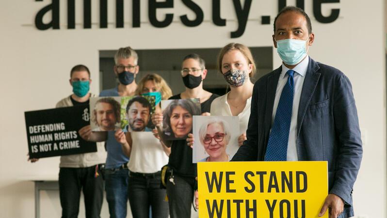"""Eine Menschengruppe mit Protestschildern """"We stand with you"""" und Porträts in den Händen, sowie Mundschutzmasken steht in einem Raum und guckt in die Kamera. Im Hintergrund an der Wand steht: amnesty.de"""