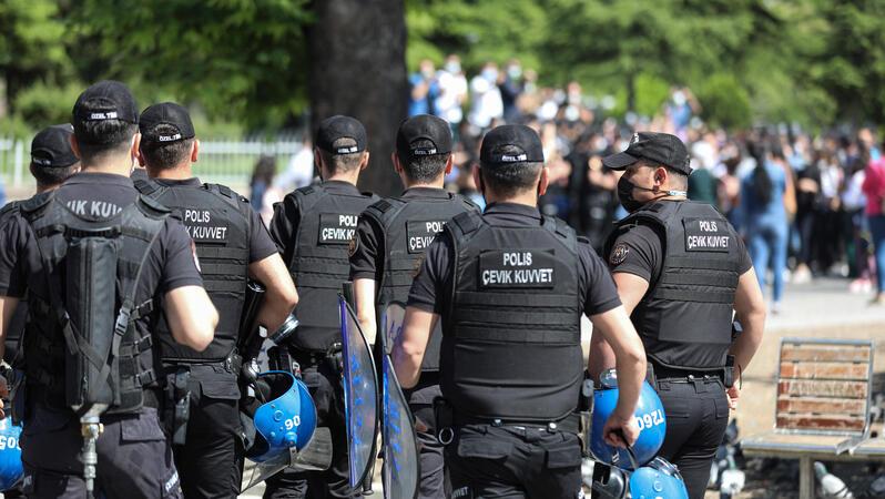 Auf dem Foto sind mehrere Polizisten von hinten zu sehen. Sie sind schwarz uniformiert und tragen Schutzwesten. In den Händen tragen sie Helme und Schilde. Etwas weiter im Hintergrund ist unscharf eine Versammlung zu erkennen.