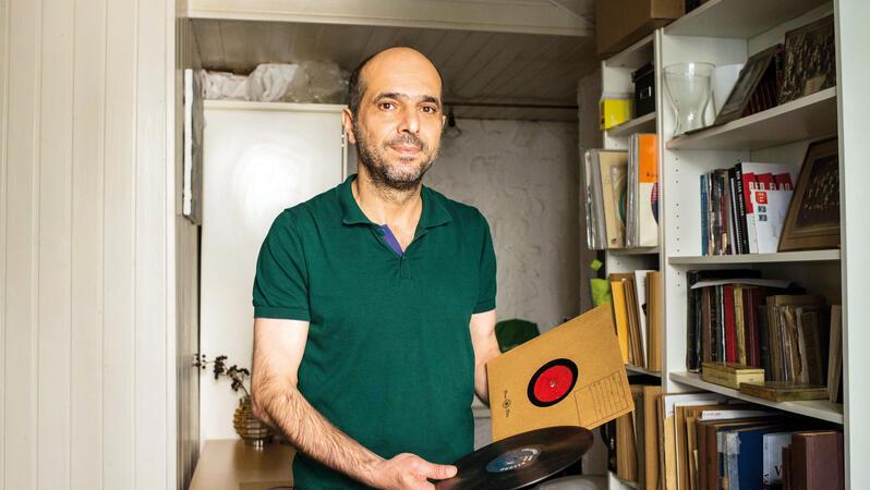 Ein Mann mit Halbglatze und Bart trägt ein Polohemd, steht in einem Raum vor einem Regal und hält Schallplatten in der Hand.