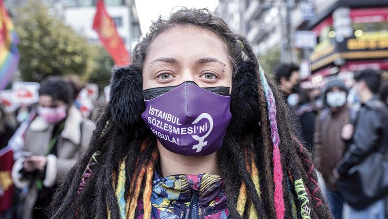 Eine Frau mit Dreadlocks und einem Augenbrauenpiercing trägt während einer Demonstration einen Mundnasenschutz.